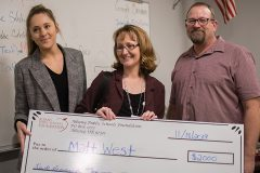 APSF Executive Director Aimee Addison presenting a grant check to teacher Matthew West